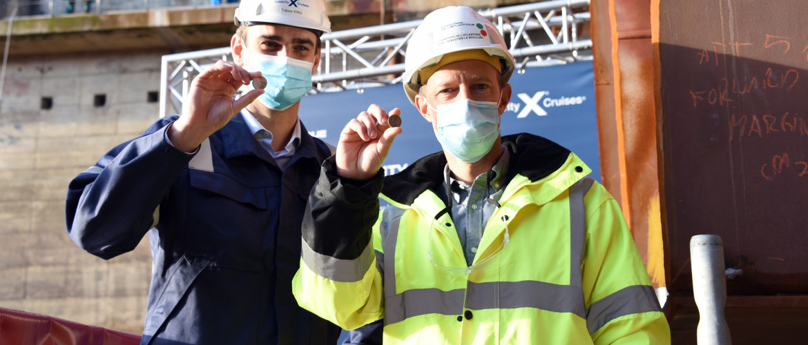 "Tobias King, Celebrity Cruises' Edge Series Project Manager, and Sébastien Le Boulluec, Chantiers de l'Atlantique's Edge Series Project Manager, hold the ceremonial ""good fortune"" coin for Celebrity Beyond as the ship's keel is laid (November 2020)"
